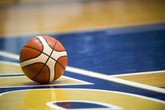 Palla di pallacanestro sopra il pavimento nella palestra fotografia stock