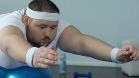 Palla di rilassamento di forma fisica dell'uomo obeso dopo il complesso, il potere e la resistenza domestici di allenamento stock footage