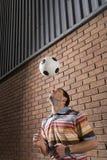 Palla di rimbalzo dell'uomo fuori dalla testa in portico fotografia stock libera da diritti