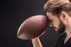 Palla di rugby barbuta arrabbiata della tenuta dell'uomo sul nero fotografie stock libere da diritti