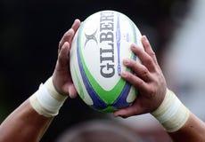 Palla di rugby in mani Immagine Stock