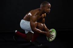 Palla di rugby senza camicia della tenuta dell'uomo di vista laterale fotografie stock libere da diritti
