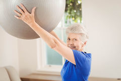 Palla di sollevamento di esercizio della donna senior mentre esercitandosi Fotografia Stock