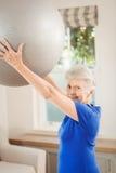 Palla di sollevamento di esercizio della donna senior mentre esercitandosi Fotografia Stock Libera da Diritti
