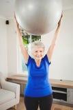Palla di sollevamento di esercizio della donna senior mentre esercitandosi Immagine Stock