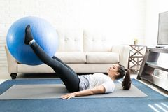 Palla di sollevamento di esercizio della donna adatta con le gambe Immagini Stock Libere da Diritti