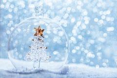 Palla di vetro di Natale con l'albero di cristallo dentro in neve Fotografia Stock