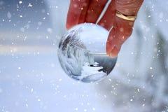 Palla di vetro trasparente che riflette un lago congelato di inverno Fotografia Stock