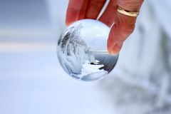Palla di vetro trasparente che riflette un lago di inverno Immagine Stock