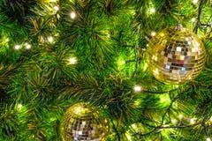 Palla dorata di natale sull'albero di Natale del fronte con litghting principale fotografia stock