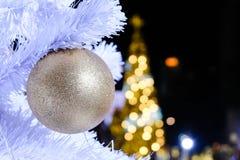 Palla dorata di natale sull'albero falso di natale bianco con le sedere della sfuocatura immagine stock libera da diritti