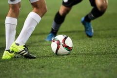 Palla ed i piedi di un calciatore Immagini Stock
