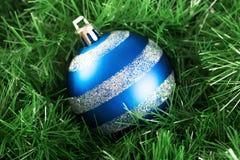 Palla operata di natale con la decorazione isolata su erba Immagini Stock