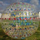Palla-pareggiare trasparente della foto - Zorba con delle le linee radiali colorate multi sui precedenti di cielo blu Fotografia Stock