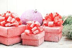 Palla porpora di Natale con i contenitori di regalo rossi Fotografie Stock Libere da Diritti