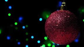 Palla rossa della decorazione di Natale sopra la ghirlanda del bokeh sui precedenti stock footage