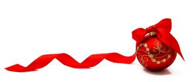 Palla rossa di natale con il nastro su un fondo bianco Fotografie Stock