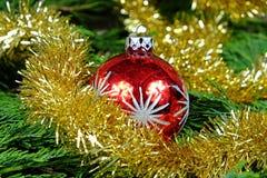 Palla rossa di Natale con le stelle d'argento intorno alla sua catena di natale nel colore dell'oro Immagini Stock Libere da Diritti