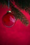 Palla rossa di natale sull'albero di natale sul fondo rosso del bokeh Carta di Buon Natale Immagine Stock Libera da Diritti