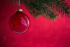 Palla rossa di natale sull'albero di natale sul fondo rosso del bokeh Carta di Buon Natale Immagine Stock