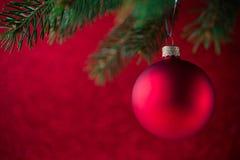 Palla rossa di natale sull'albero di natale sul fondo rosso del bokeh Carta di Buon Natale Fotografie Stock