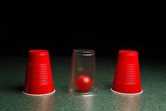 Palla rossa nascosta sotto la chiara tazza fotografia stock libera da diritti