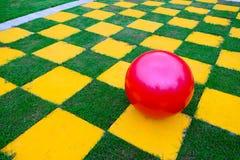 Palla rossa sul campo giallo verde di griglia di scacchi Fotografie Stock Libere da Diritti