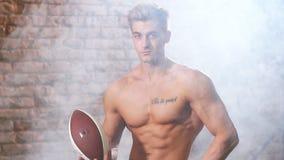 Palla senza camicia della tenuta del giocatore di football americano, movimento lento video d archivio
