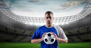 Palla sicura della tenuta del calciatore allo stadio Immagini Stock Libere da Diritti