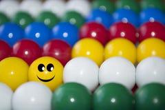Palla sorridente fra le palle colorate immagini stock