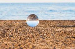 Palla trasparente di vetro sul fondo del mare e Fotografia Stock Libera da Diritti
