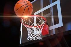 Pallacanestro che si dirige alla rete ad un'arena di sport con il chiarore della lente immagini stock