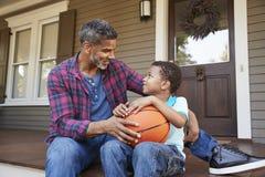Pallacanestro di And Son Discussing del padre sul portico della casa immagini stock libere da diritti