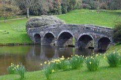 Palladian Bridge and Lake, Stourhead, Stourton, Wiltshire, England. The Palladian Bridge and Lake with narcissi and daffodils in Spring, Stourhead, Stourton Royalty Free Stock Image