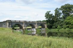Palladian Bridge over Cutler Brook River in Kedleston, Derby, Derbyshire, England, Europe. Outdoor view of River Cutler Brook bank and its ornate bridge wih a Stock Images