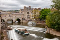Palladian Pulteney Bridge and the weir at Bath Somerset South We. BATH, UK - JUN 12, 2013: City scene with weir on the River Avon near Palladian Pulteney Bridge Stock Photography