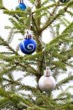 Palle blu e d'argento di Natale che appendono su un albero di Natale Fotografie Stock