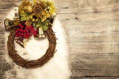 Palle, campane, corona e stella brillanti di Natale dell'oro su fondo di legno con neve Immagini Stock Libere da Diritti