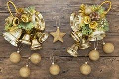 Palle, campane e stella brillanti di Natale dell'oro su fondo di legno Fotografia Stock