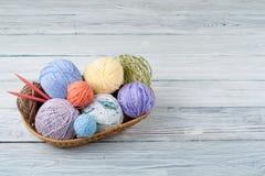 Palle colorate del filato su un fondo di legno Matasse del filato di lana per tricottare Palle di lana dei colori differenti per Fotografia Stock