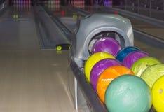 Palle da bowling sui precedenti dei vicoli di bowling Fotografia Stock