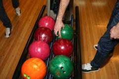Palle da bowling Vicolo di bowling L'uomo prende una palla Colori chiari Fotografie Stock
