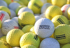 Palle da golf bianche e gialle di pratica al campo da golf che colpisce gamma Immagini Stock