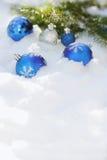 Palle decorative di Natale sulla neve e sul brunch dell'albero di Natale all'aperto Fotografia Stock
