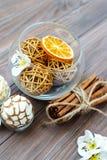 Palle decorative ed arancia secca in palla di vetro con cannella su una tavola di legno con vari bei oggetti Fotografia Stock Libera da Diritti