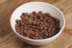 Palle del cereale del cioccolato con latte in ciotola bianca per la prima colazione sulla tavola di legno Fotografia Stock