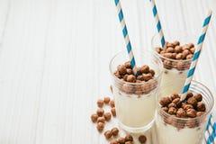 Palle del cereale del cioccolato con latte e paglie Immagini Stock