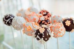Palle del cioccolato con i fiori della glassa messi sui bastoni bianchi Immagine Stock