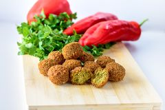 Palle del Falafel, peperone dolce e prezzemolo fresco verde su fondo di legno Il Falafel ? un alimento del Medio-Oriente tradizio immagini stock libere da diritti