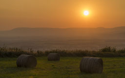 Palle del fieno con il tramonto sopra le montagne Fotografie Stock
